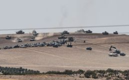 TOPSHOT - This picture taken from the Turkish Syrian border city of Karkamis in the southern region of Gaziantep, on August 24, 2016 shows Turkish army tanks and pro-Ankara Syrian opposition fighters moving two kilometres west from the Syrian Turkish border town of Jarabulus. Turkey's army backed by international coalition air strikes launched an operation involving fighter jets and elite ground troops to drive Islamic State jihadists out of a key Syrian border town. Turkey's state-run Anadolu news agency reported that pro-Ankara Free Syrian Army (FSA) rebels had already penetrated three kilometres (two miles) inside Syria towards the IS-held town of Jarabulus. The air and ground operation, the most ambitious launched by Turkey in the Syria conflict, is aimed at clearing jihadists from the town of Jarabulus, which lies directly opposite the Turkish town of Karkamis. / AFP PHOTO / BULENT KILIC